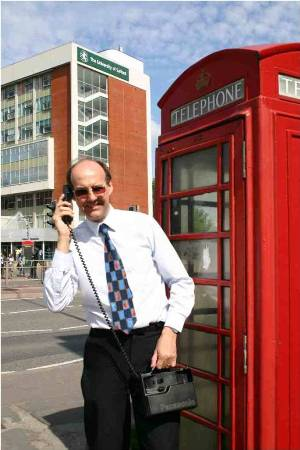 Nigel Linge using a vintage mobile phone and stood outside of a K6 telephone kiosk at the University of Salford, UK
